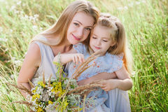 Mom and daughter in nature with a bouquet of wild flowers Royalty Free Stock Photo