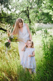 Mom and daughter in nature with a bouquet of wild flowers Royalty Free Stock Photos