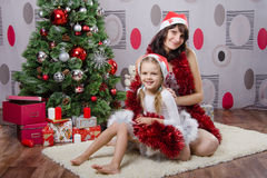 Mom and daughter near Christmas tree Stock Photo