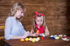 Mom and daughter paint Easter eggs royalty free stock image