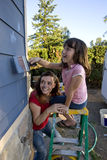 Mom and Daughter Painting a House - Vertical Royalty Free Stock Image