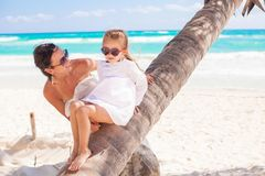 Mom and daughter on a palm tree enjoying vacations Stock Photos