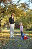 Mom and daughter in the park. Beautiful little girl carrying  her bag on the alley Stock Photography