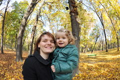 Mom and daughter in the park. Beautiful little girl playing with her mom in an autumn park Royalty Free Stock Image