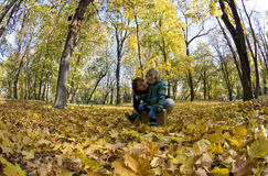 Mom and daughter in the park. Beautiful little girl playing with her mom in an autumn park Stock Images