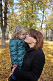 Mom and daughter in the park. Beautiful little girl kissing her mom in an autumn park Stock Images