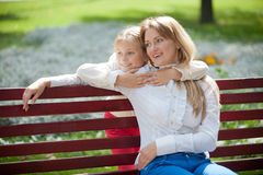 Mom and daughter on a park bench Royalty Free Stock Photo