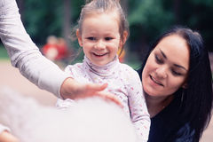 Mom and daughter in the park eating cotton candy Royalty Free Stock Photography