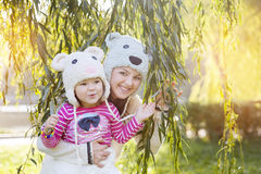 Mom and daughter in the park, in a knitted hat smiling Royalty Free Stock Photos