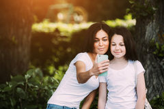 Mom and daughter. In the park make selfie royalty free stock photo