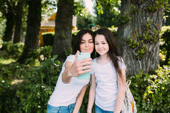 Mom and daughter. In the park make selfie stock image