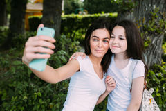 Mom and daughter. In the park make selfie stock photo