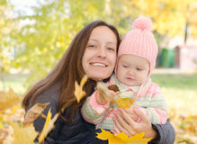 Mom and daughter in park. Mother and little daughter in the autumn park royalty free stock image