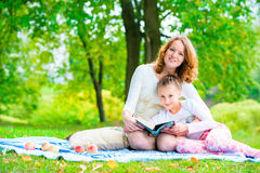 Mom and daughter in the park reading book Royalty Free Stock Photos