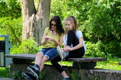 Mom and daughter in park on roller skates Stock Photos
