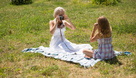Mom and daughter photograher and model. Young mom and her little girl taking pictures while sitting on blanket outdoors stock photo