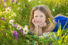 Mom and daughter on a picnic in the chamomile field. Two beautiful blondes in chamomile field on a background of horse. Mother and daughter embracing in the Royalty Free Stock Photos