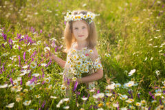 Mom and daughter on a picnic in the chamomile field. Two beautiful blondes in chamomile field on a background of horse. Mother and daughter embracing in the Stock Photo