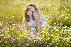 Mom and daughter on a picnic in the chamomile field. Two beautiful blondes in chamomile field on a background of horse. Mother and daughter embracing in the Stock Image