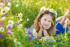 Mom and daughter on a picnic in the chamomile field. Two beautiful blondes in chamomile field on a background of horse Stock Photography
