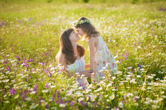 Mom and daughter on a picnic in the chamomile field. Two beautiful blondes in chamomile field on a background of horse. Mother and daughter embracing in the Royalty Free Stock Image