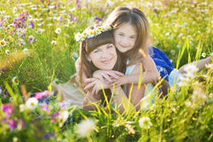 Mom and daughter on a picnic in the chamomile field. Two beautiful blondes in chamomile field on a background of horse. Mother and daughter embracing in the Royalty Free Stock Photography