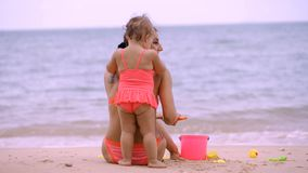 Mom and daughter in pink swimsuits on the shore of a beautiful beach playing in the sand with children`s beach toys stock photos