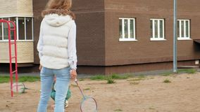 Mom and daughter play badminton outdoors stock video footage