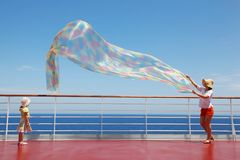 Mom and daughter play with chiffon scarf on deck Stock Images