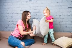 Mom and daughter play on the couch with pillows fight. Dressed in bright stylish clothes in a room stock photos