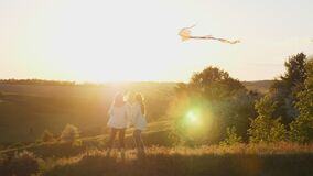Mom and daughter play with a kite at sunset