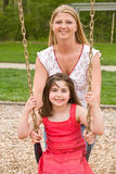 Mom and Daughter Playing. Mom Pushing Daughter on Swing stock photo