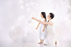 Mom and daughter playing balloons. Mom and cute daughter playing balloons Royalty Free Stock Images