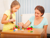 Mom and daughter playing with blocks Stock Images