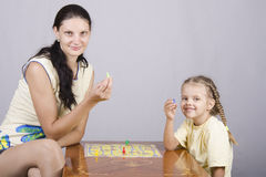 Mom and daughter playing a Board game Stock Image