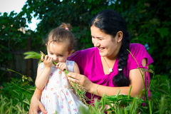 Mom and daughter playing in the field, sitting on the grass. Royalty Free Stock Image