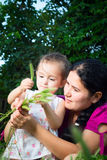 Mom and daughter playing in the field, sitting on the grass. Royalty Free Stock Photo
