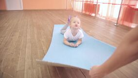 Mom and daughter are playing in the gym. A woman rolls her little daughter to a gym on a rug for sports stock video footage