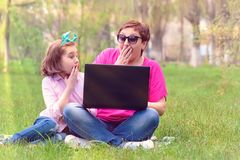 Mom and daughter playing in the laptop outdoors. Laughing and enjoying the summer sun on the green grass in the park royalty free stock image