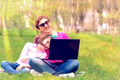 Mom and daughter playing in the laptop outdoors. Laughing and enjoying the summer sun on the green grass in the park stock image