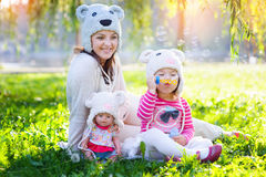 Mom and daughter playing in the park with a doll in caps Royalty Free Stock Images