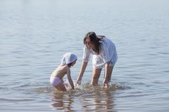 Mom and daughter are playing in the river. Happy family royalty free stock photo