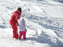 Mom and daughter playing in the snow Royalty Free Stock Photo