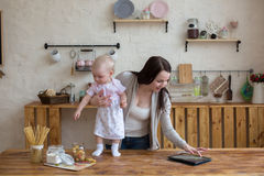Mom and daughter playing together with tablet in home interior l Royalty Free Stock Photos