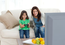 Mom and daughter playing video games together. In the living room Royalty Free Stock Images
