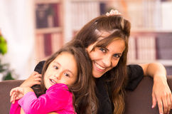 Mom and daughter posing happily indoors with heads Stock Photos