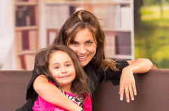Mom and daughter posing happily indoors in sofa Royalty Free Stock Images