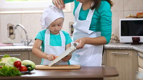 Mom and daughter are preparing carrots. Mom and daughter in the kitchen preparing carrots stock video footage
