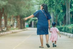 Mom and daughter pupil girl holding hand in hand on street go to the classroom royalty free stock image