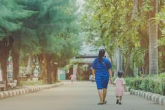 Mom and daughter pupil girl holding hand in hand on street go to the classroom stock photography